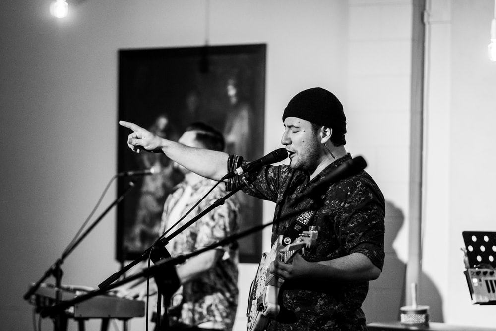 grayscale photography of singing man playing guitar