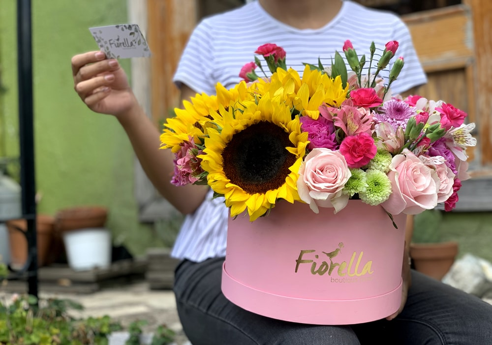 assorted-color petaled flowers in pink vase on woman's lap