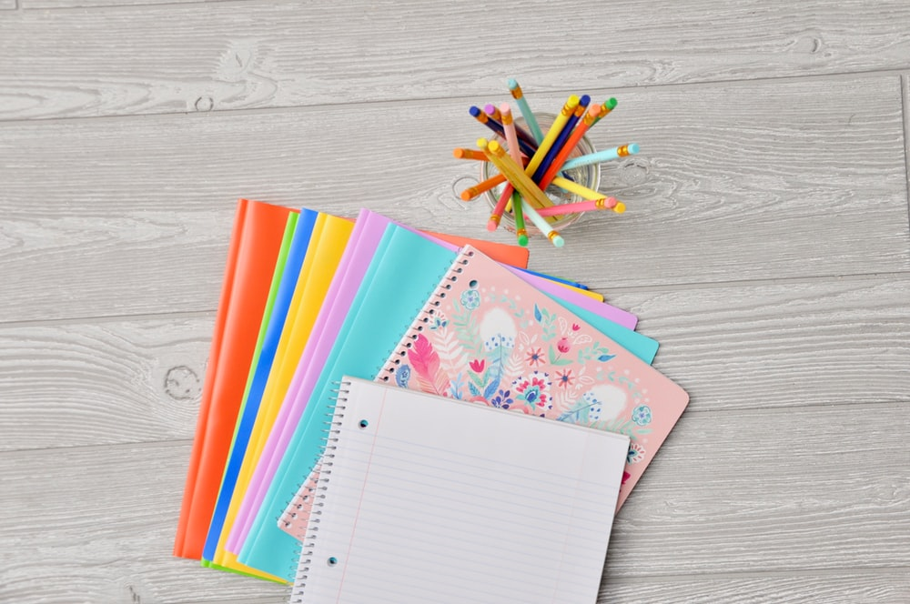 pile of assorted-color notebooks on brown wooden table