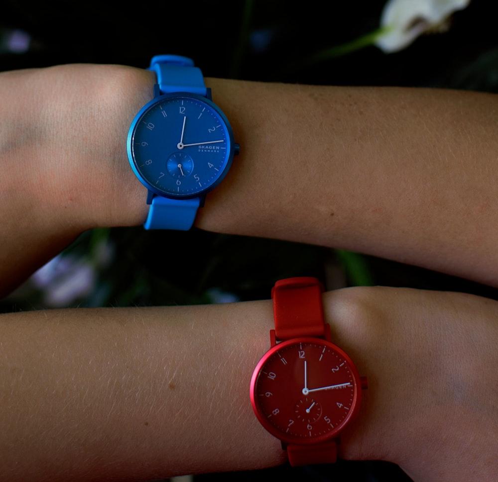 person wearing round blue analog watch displaying 12:14 time