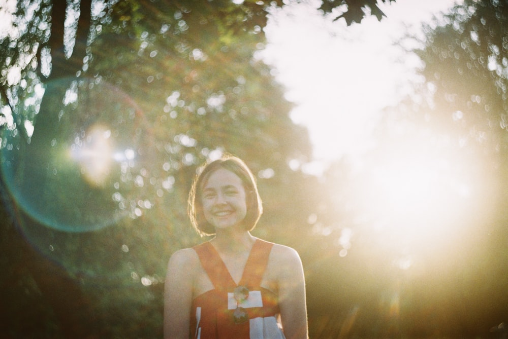 sun rays coming through woman wearing orange sleeveless top standing and laughing during daytime