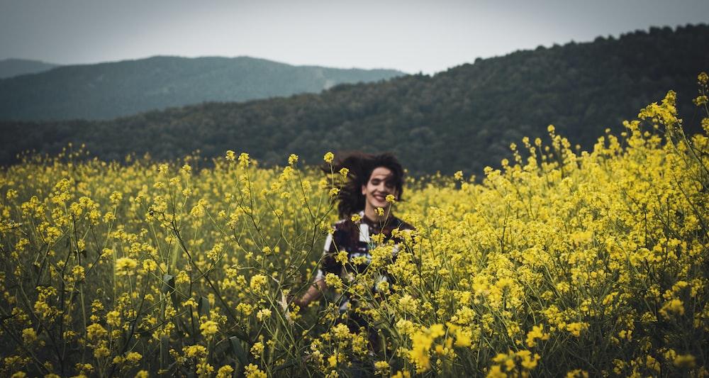 woman in black top on yellow flower garden