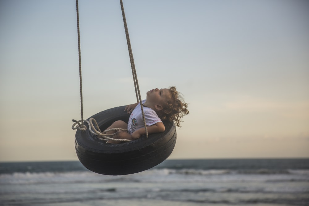 girl sitting on tire swing at daytime
