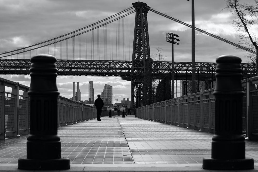 grayscale photo of person walking near bridge