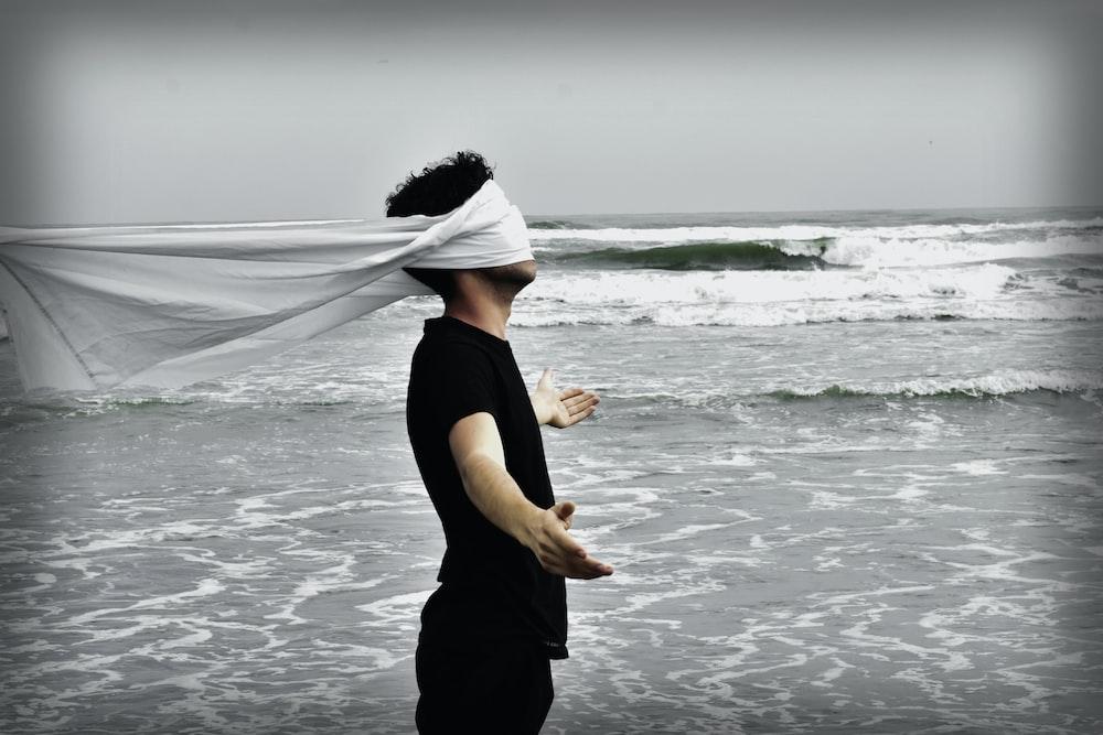 man standing on seashore during daytime