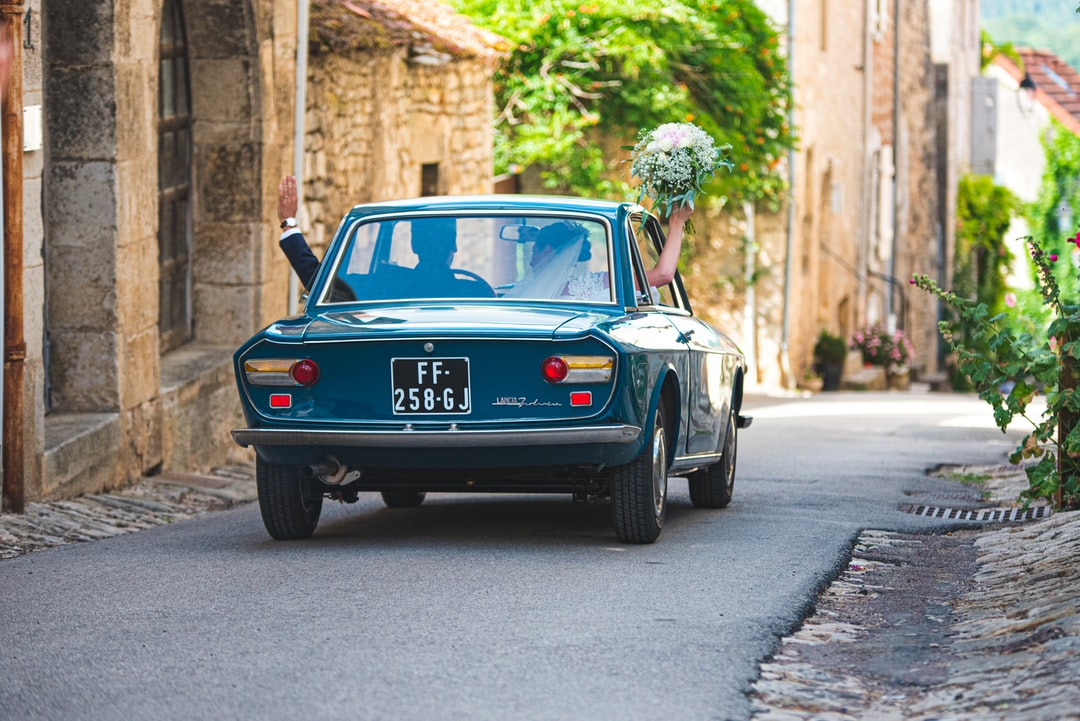 Fresh romantic married couple rides in vintage car after religious ceremony of wedding. France, Flavigny
