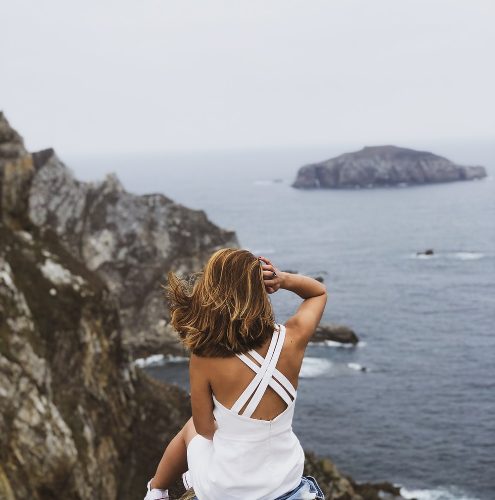 woman sitting and overlooking body of water