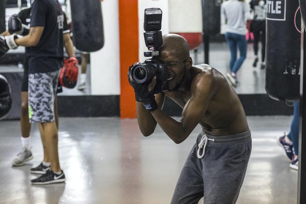 man taking picture while using DSLR camera