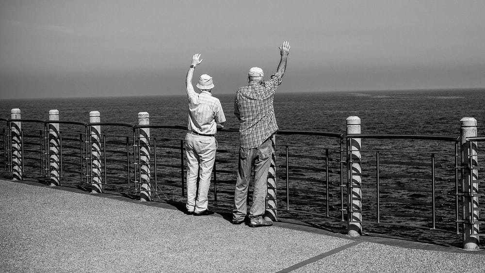 grayscale photography of two person raising both hands