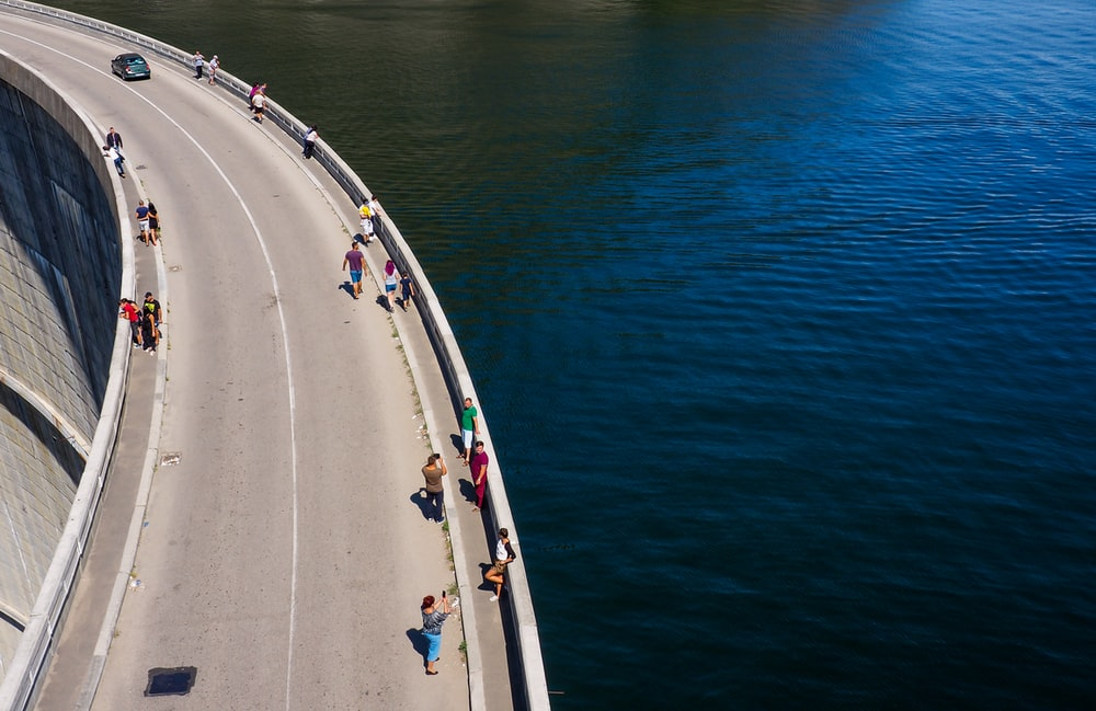 people standing on gray concrete road over calm water