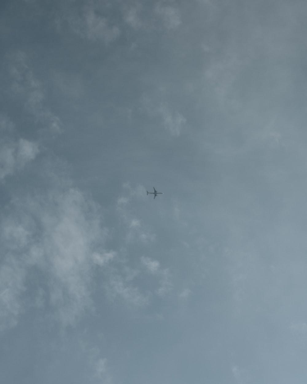 plane under white clouds