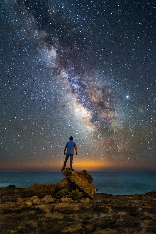 man standing on rock facing ocean under starry night