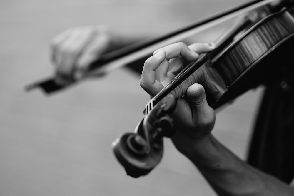 grayscale photo of person playing violin