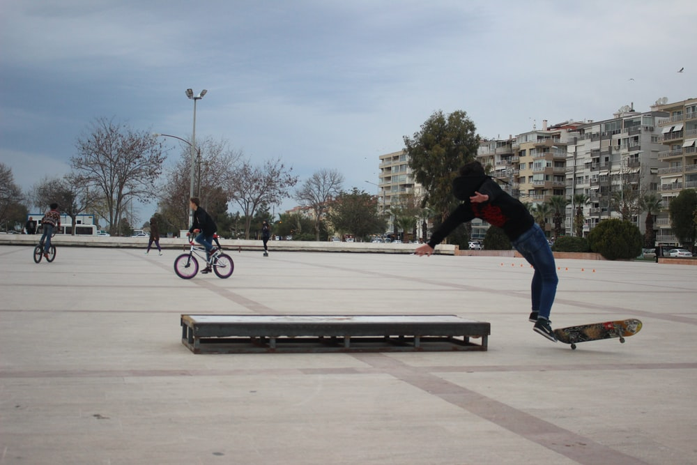 man riding at black and brown skateboard