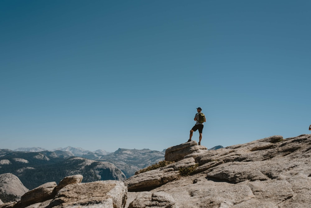 man standing on brown rock formations