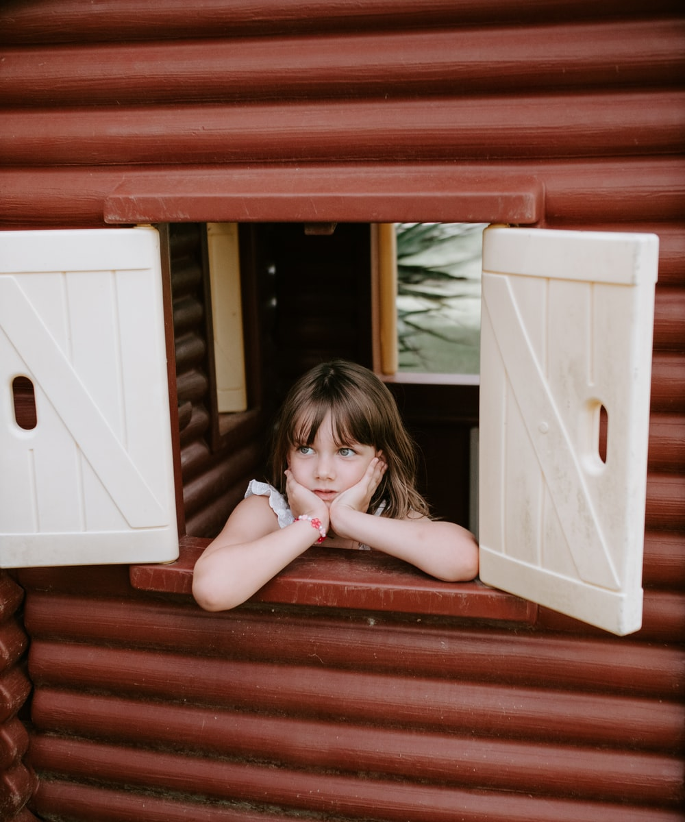 woman leaning on white and brown playhouse window