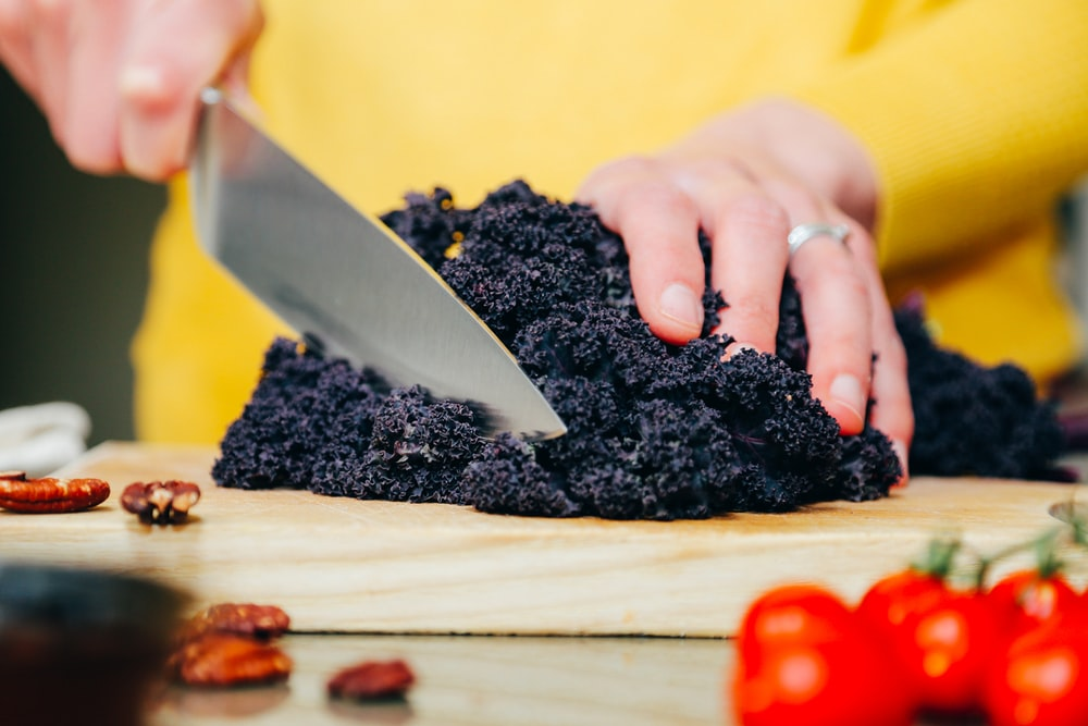 person slicing a black-leafed vegetable
