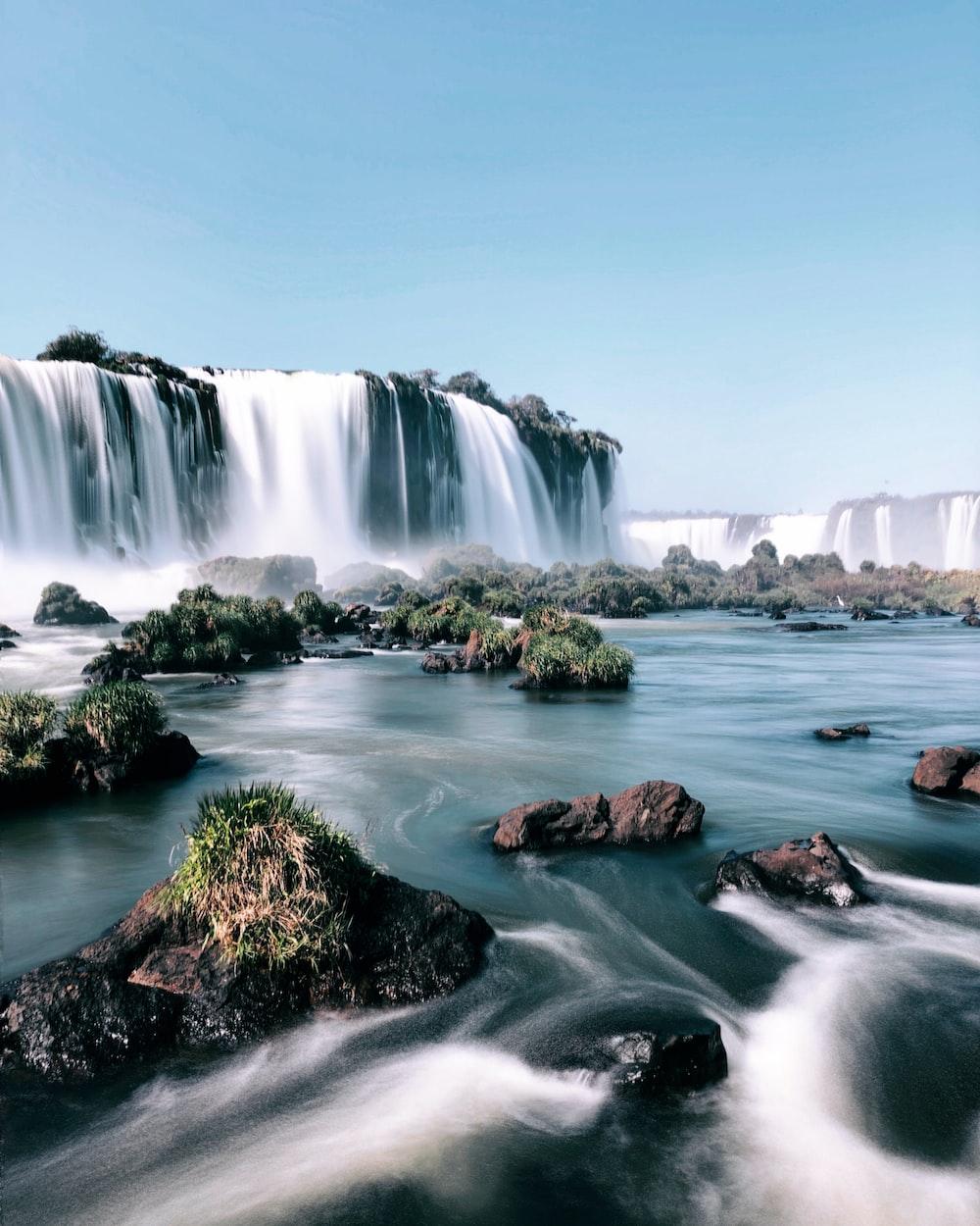 waterfalls under clear sky during daytime digital wallpaper