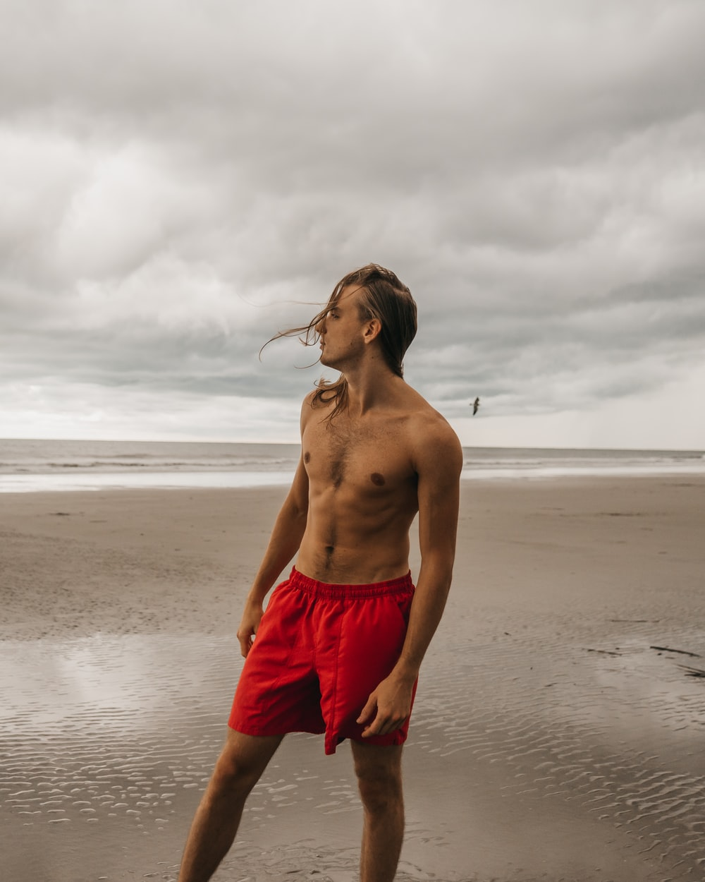 man in red shorts standing on seashore during daytime