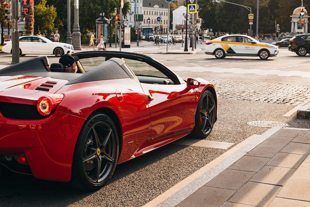 日中の道路上の車の近くの道路脇にある赤いコンバーチブルクーペの運転席に座っている人