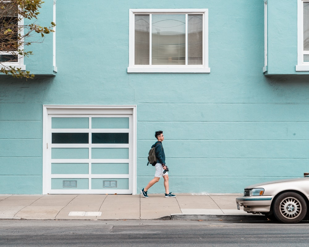 man walking outside house beside car