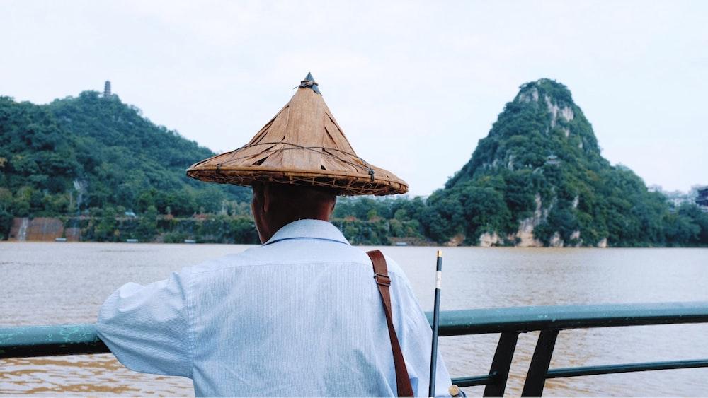 man wearing white dress shirt across body of water