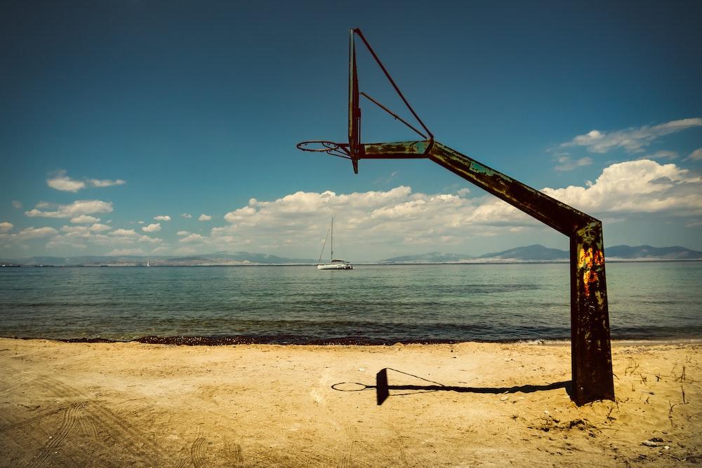 black basketball hoop on seashore during daytime