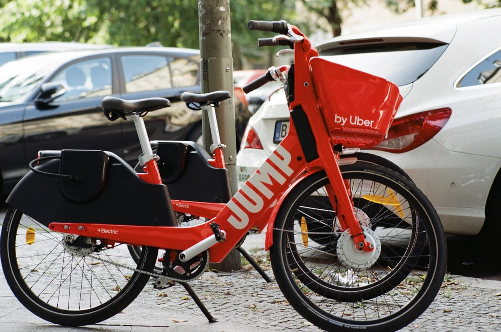 red commuter bike beside vehicle