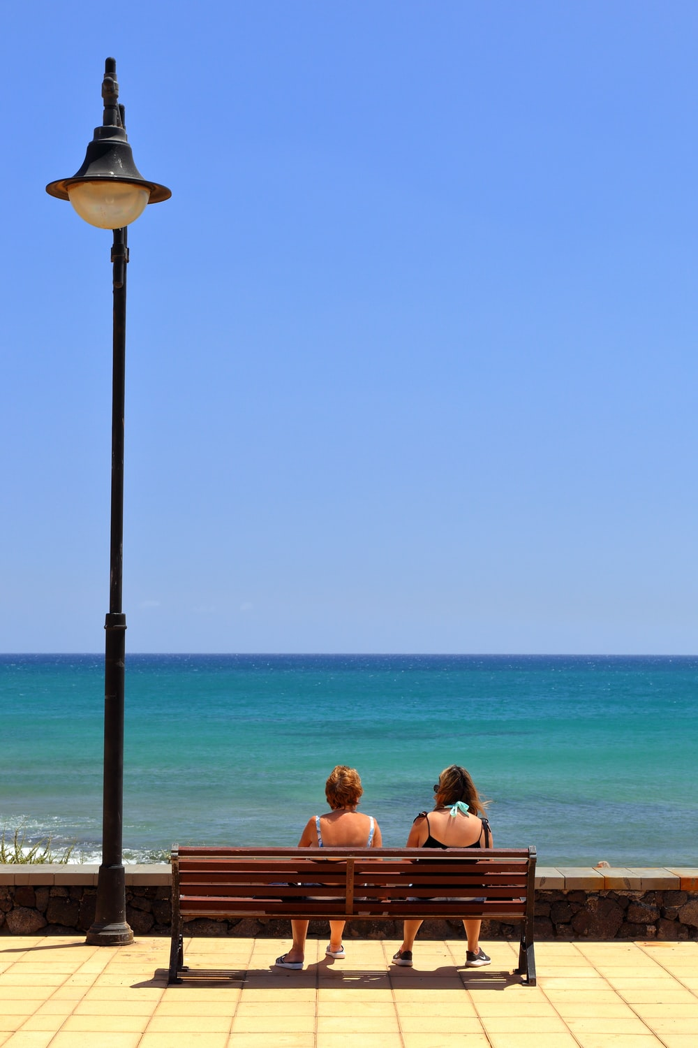 two women sitting on wooden bench front of sea