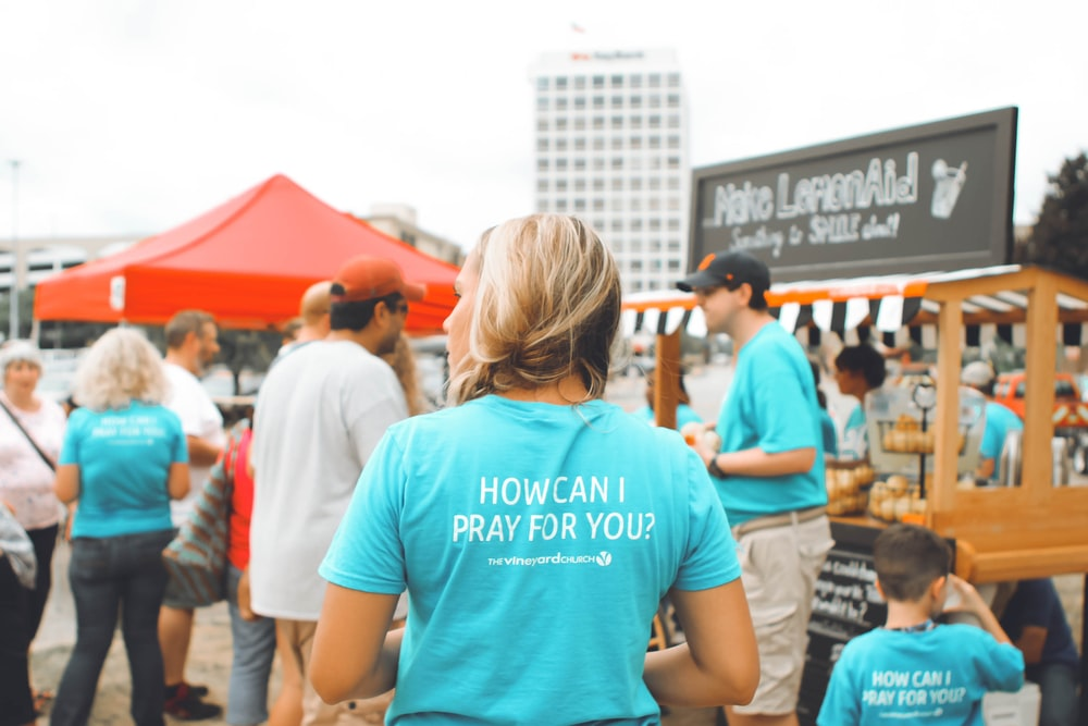 woman wearing teal t-shirt standing front of peopled