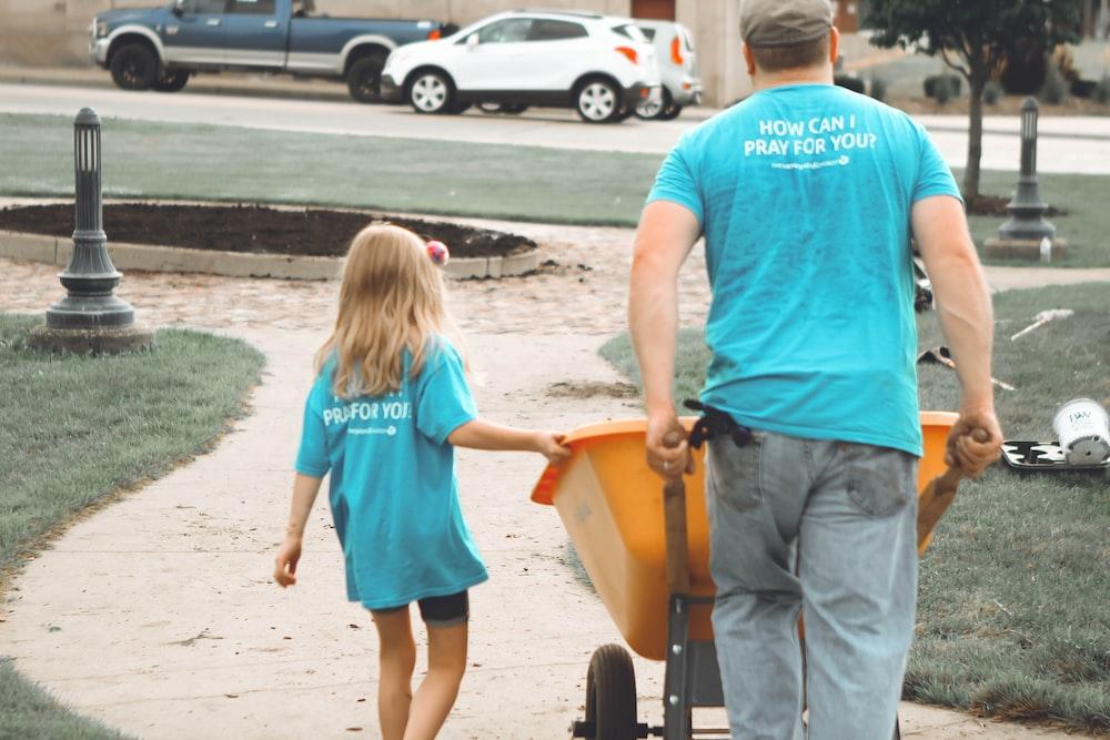 man carrying orange wheelbarrow during daytime