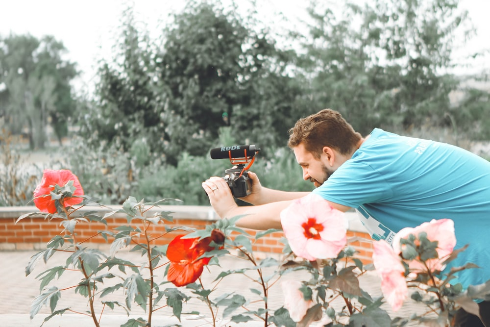 man in blue top using black DSLR camera outdoors