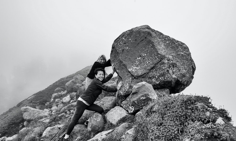 grayscale photography of two women pushing rock