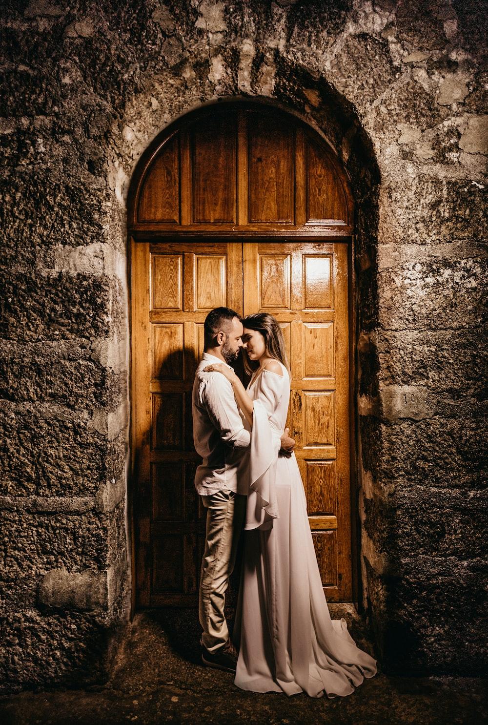 man and woman standing in front of wooden double door