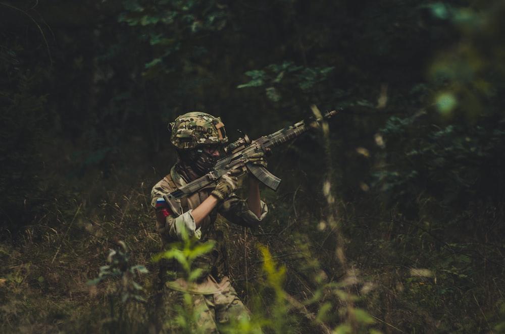 man pointing assault rifle near trees