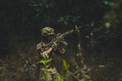 man pointing assault rifle near trees military zoom background