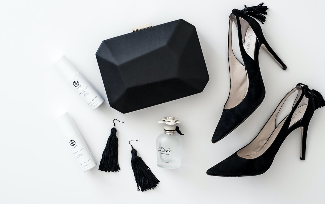 Black and white flat lay with perfume, tassel earrings, clutch bag and heels.