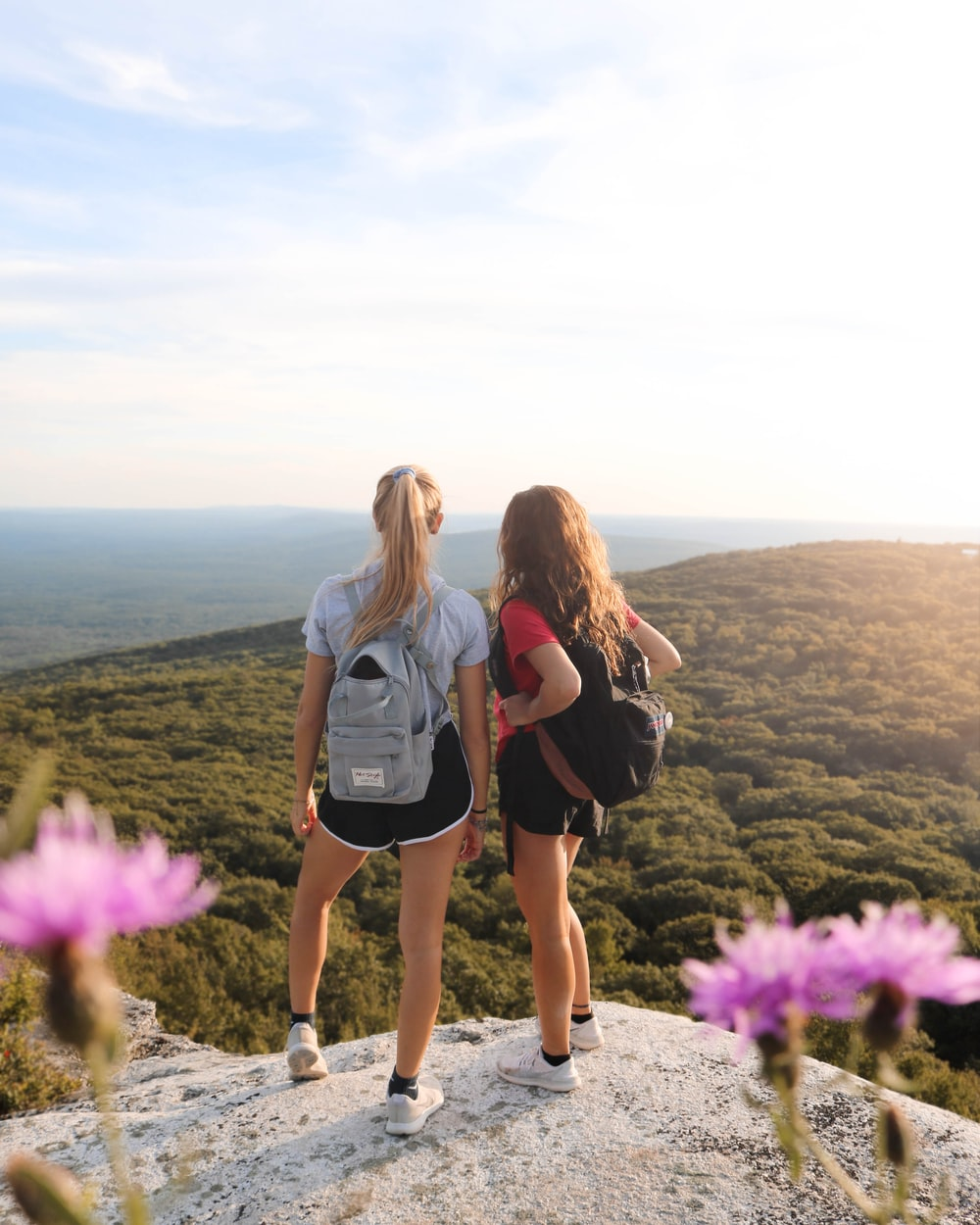 two women standing on rock cliff