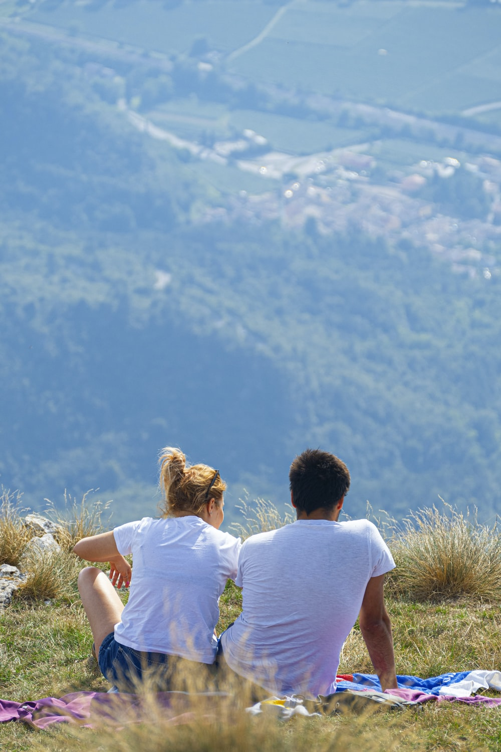 man iand woman in white shorts sitting on hill