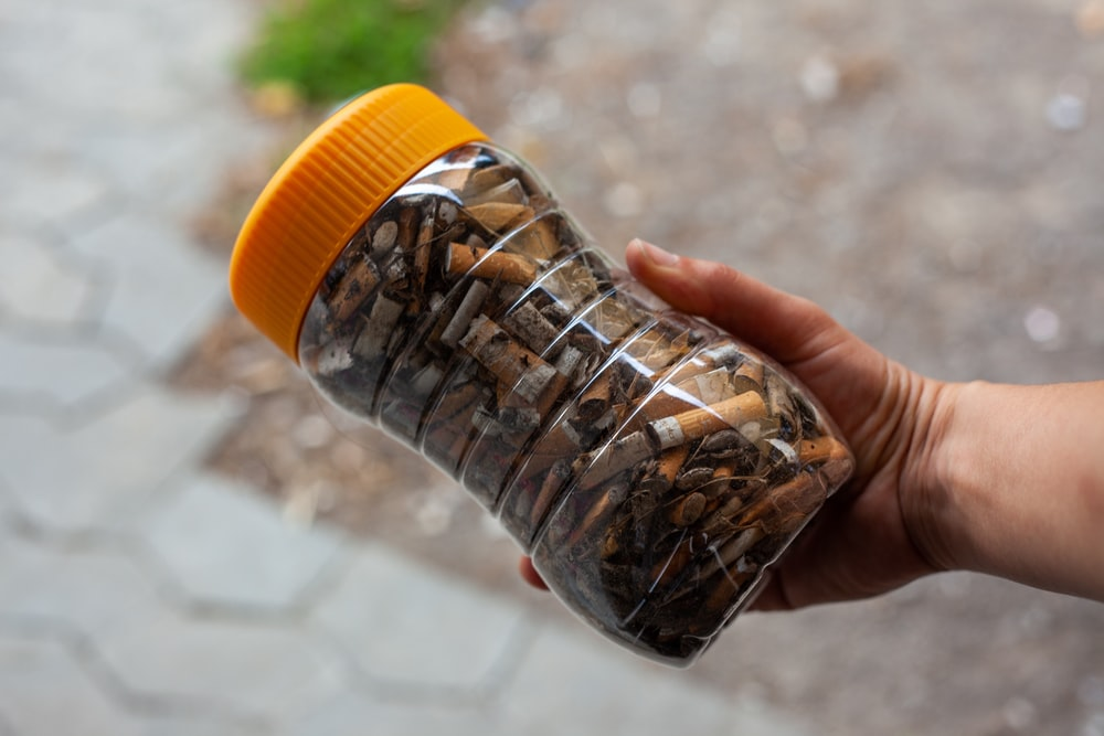 person holds jar of cigarette butts