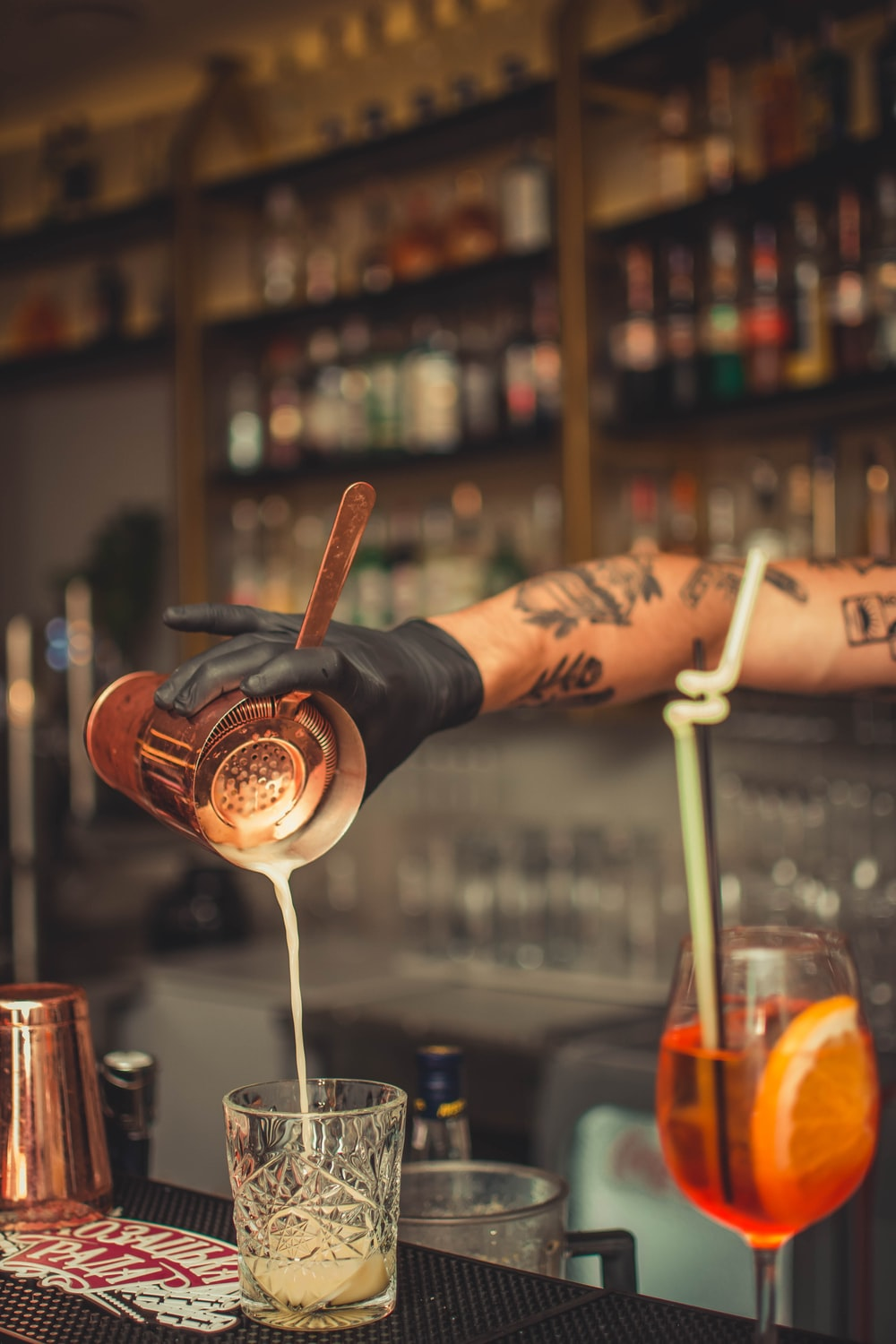 person pouring brown liquid into clear cut-glass shot glass inside bar