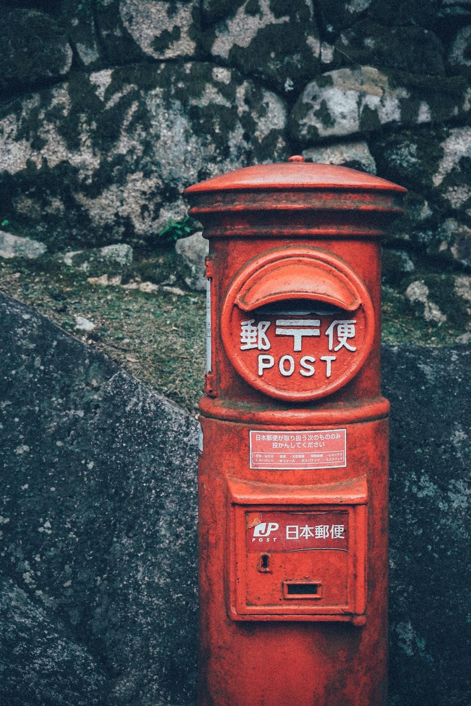 orange public mailbox beside wall