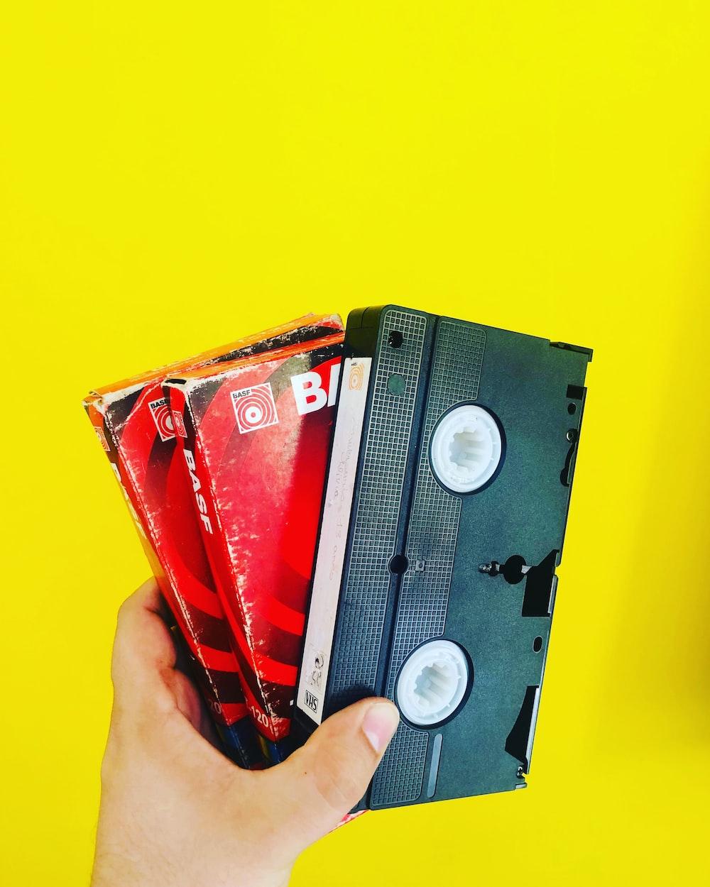 person holding black cassette