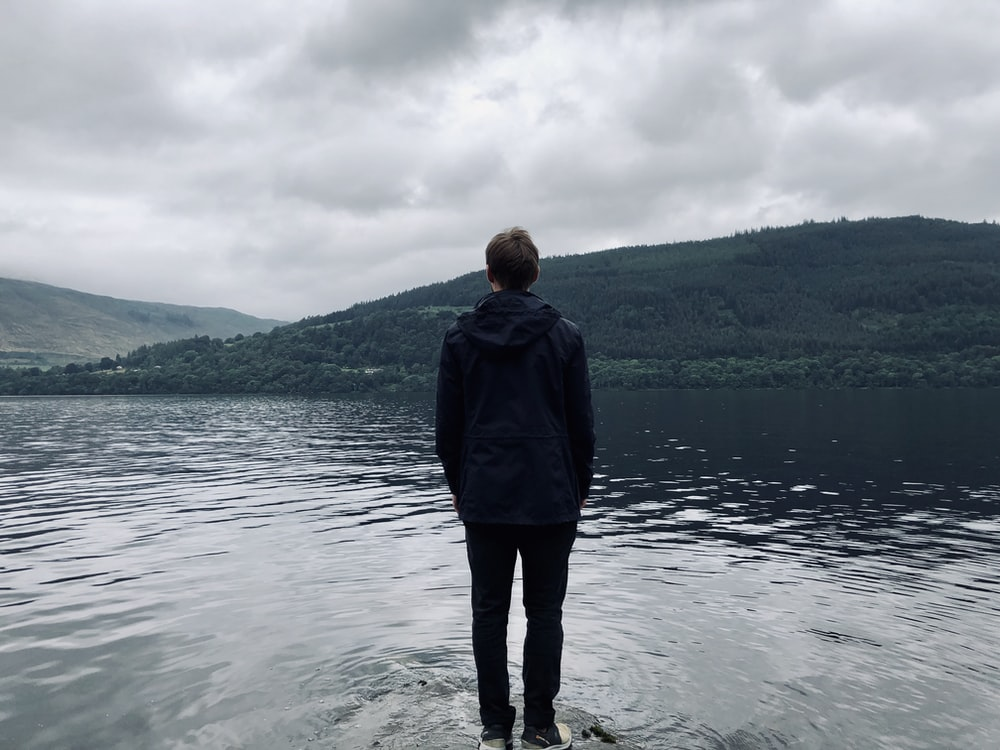 man standing and facing on river under white skies during daytime