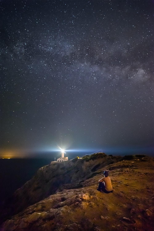 person sitting near cliff under starry night