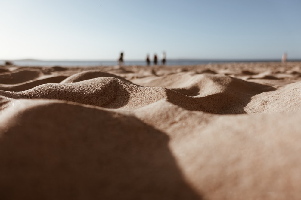 low-angle photography of sand under white sky
