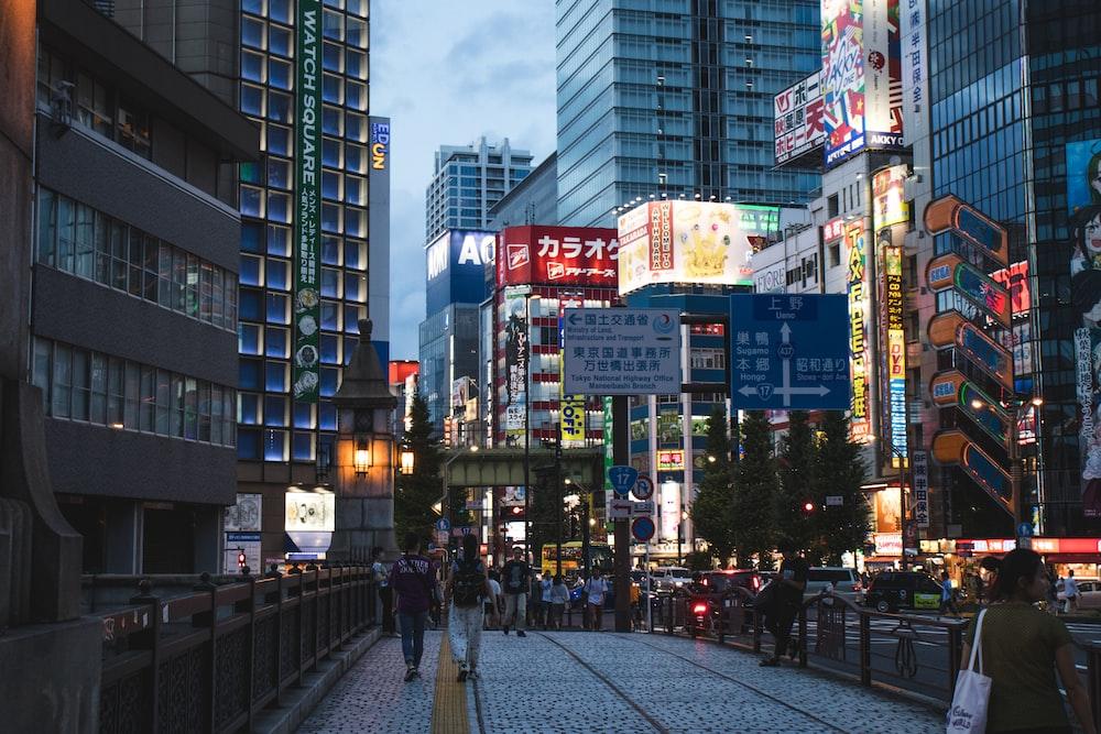 people standing between high buildings