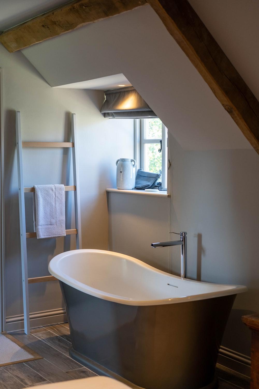 wooden ladder rack near white and black ceramic bathtub