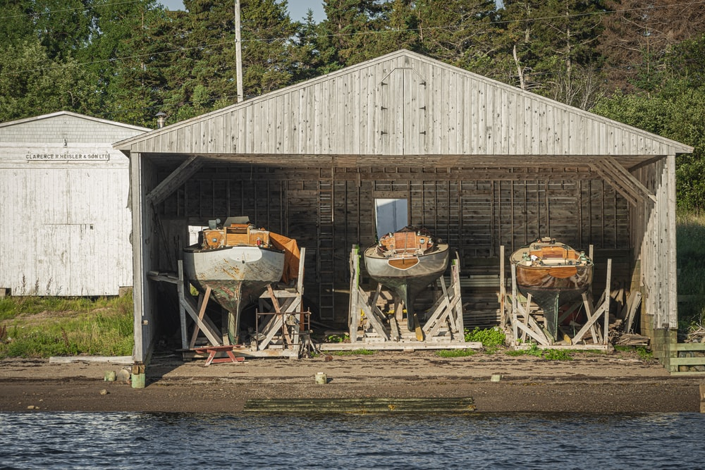 boats in wooden shed near body of water during daytime