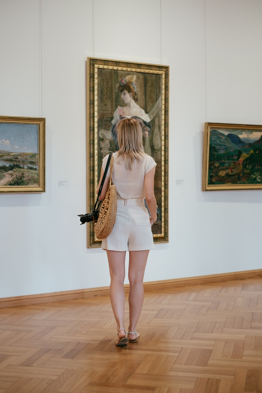 woman wearing white shorts in front of painting